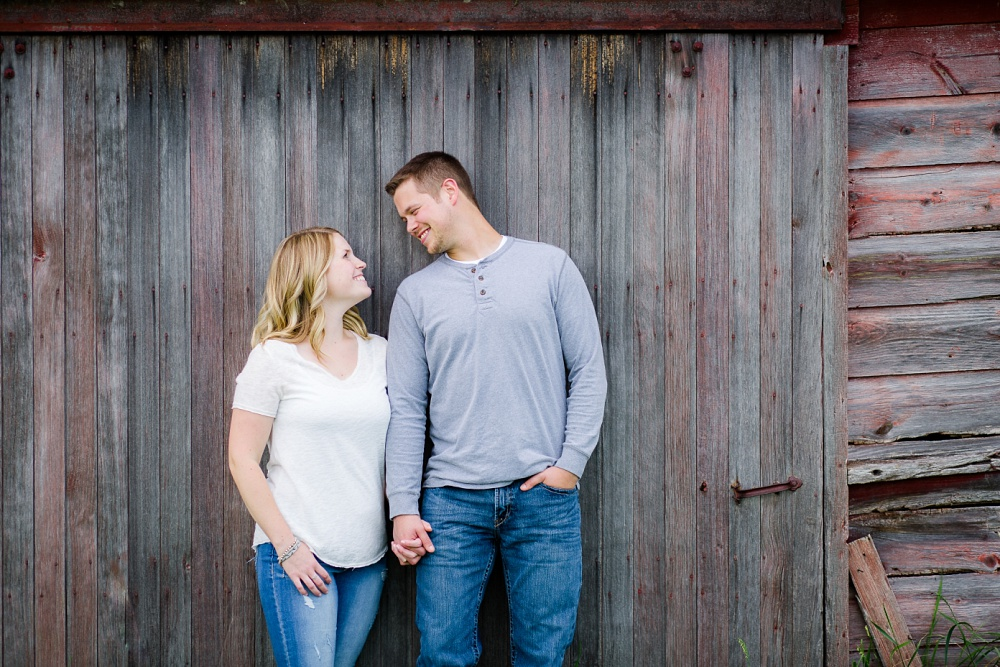 Couple smiling in front of old barn wood | Outdoor, country styled engagement session near Audubon, MN | Amer Langerud Photography