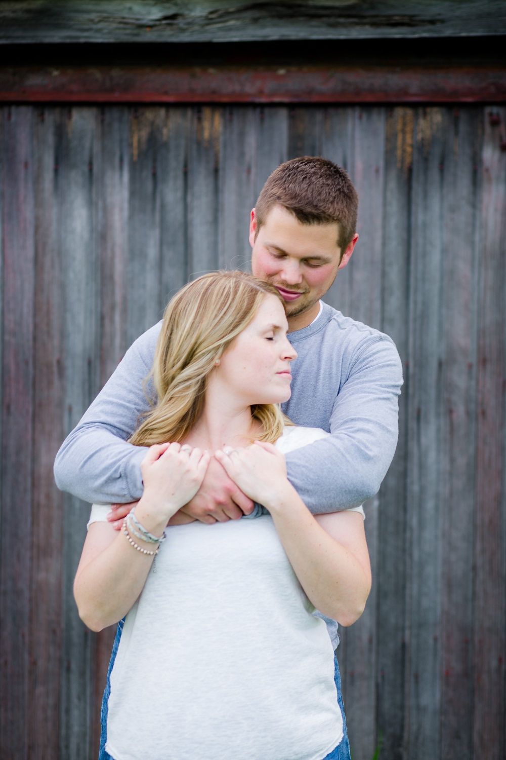 Couple snuggling in front of old barn wood | Outdoor, country styled engagement session near Audubon, MN | Amer Langerud Photography