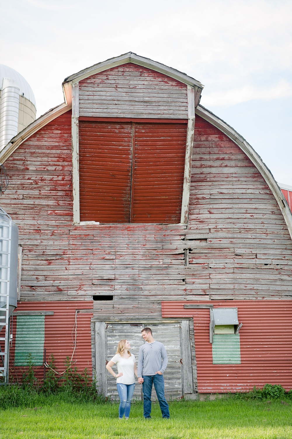 Couple standing in front of old dairy barn | Outdoor, country styled engagement session near Audubon, MN | Amer Langerud Photography