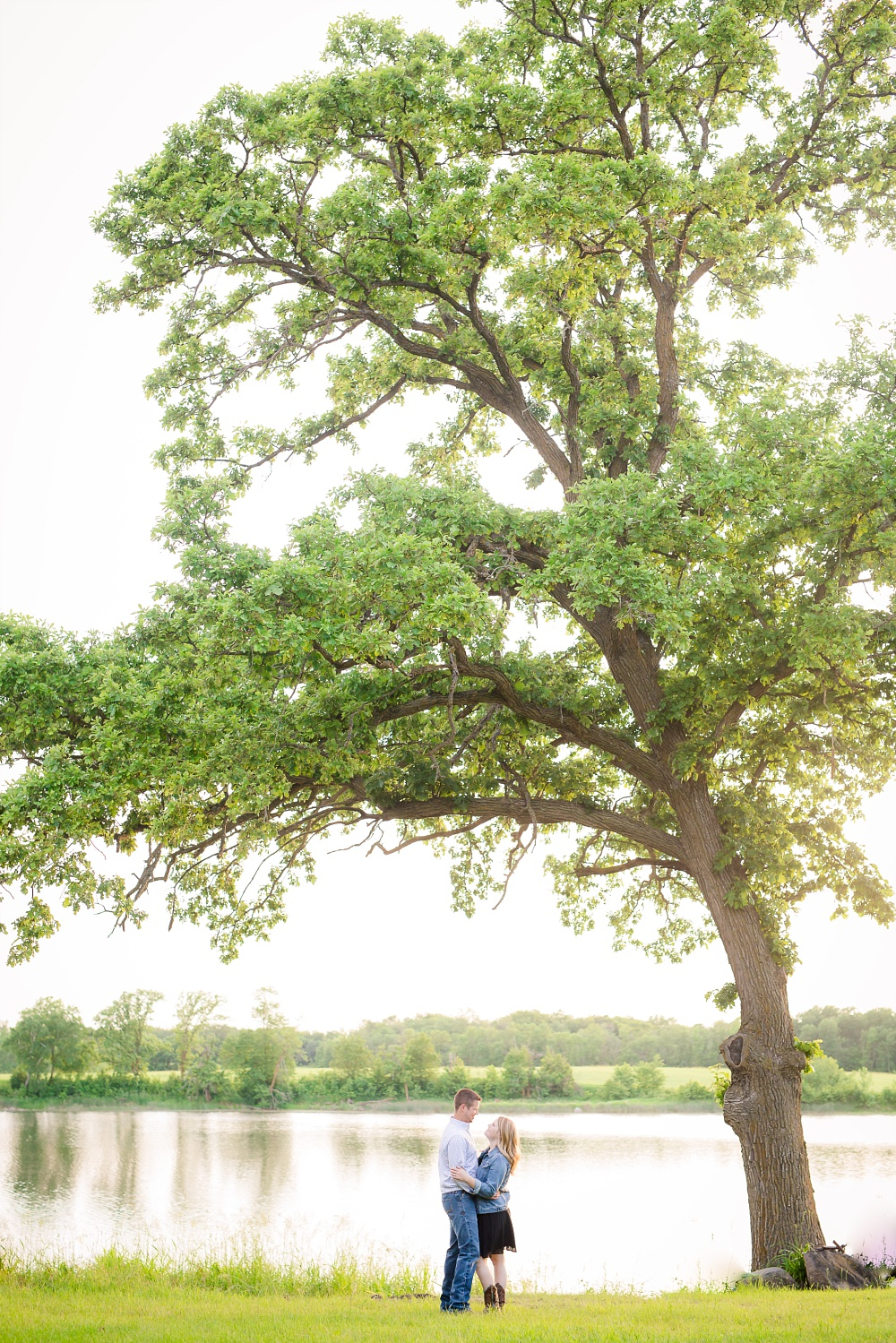 Couple standing under large oak tree in front of a lake | Outdoor, country styled engagement session near Audubon, MN | Amer Langerud Photography