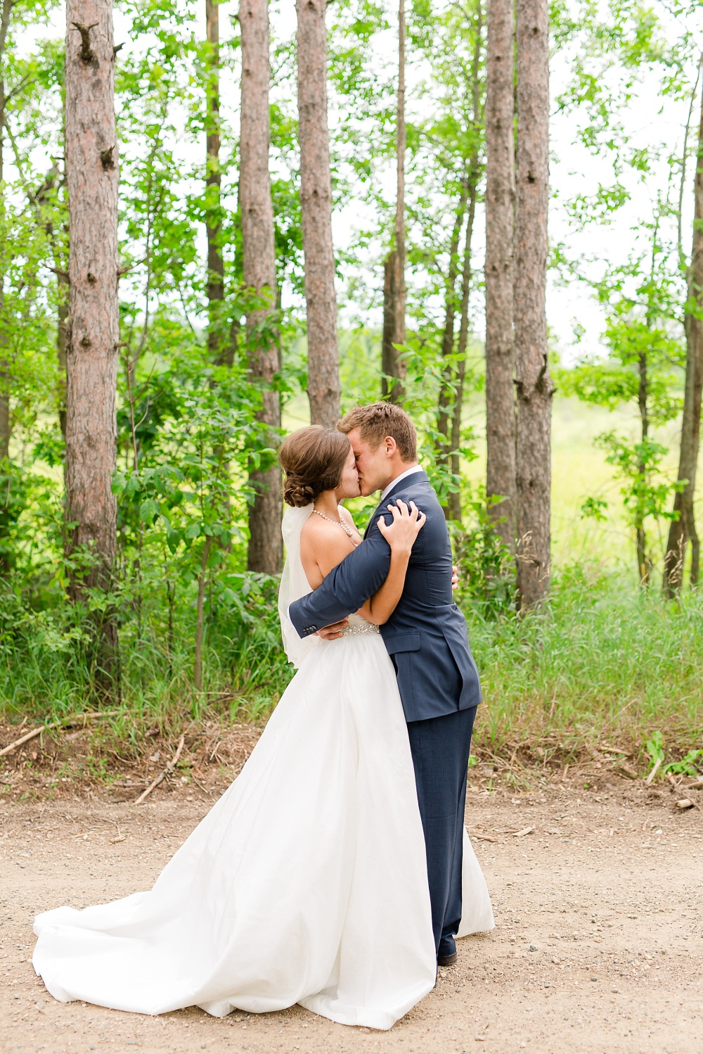 Wolf Lake, MN Country Styled Wedding, White Dress, Blue Suite | Photographed by Amber Langerud Photography | Bride and Groom Hugging after first look