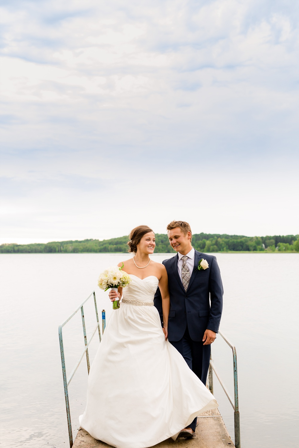 Wolf Lake, MN Country Styled Wedding, White Dress, Blue Suite | Photographed by Amber Langerud Photography | Bride & Groom Walking on a Dock