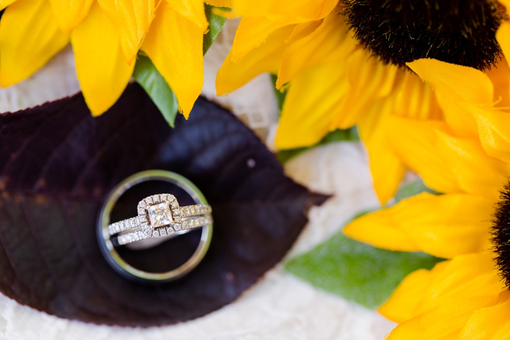 Detroit Lakes, MN Country Styled Wedding at Trinity Lutheran Church & Holmes Ballroom Photographed by Amber Langerud Photography | Rings styled with sunflowers