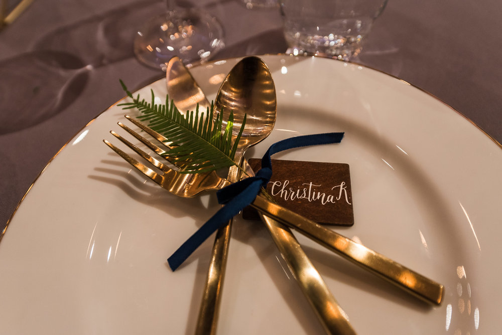 Gold Silverware Place Setting tied with Navy ribbon, fern and wood place card