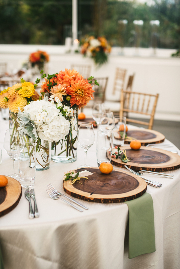 Wood wedding charger place setting with orange and white centerpieces