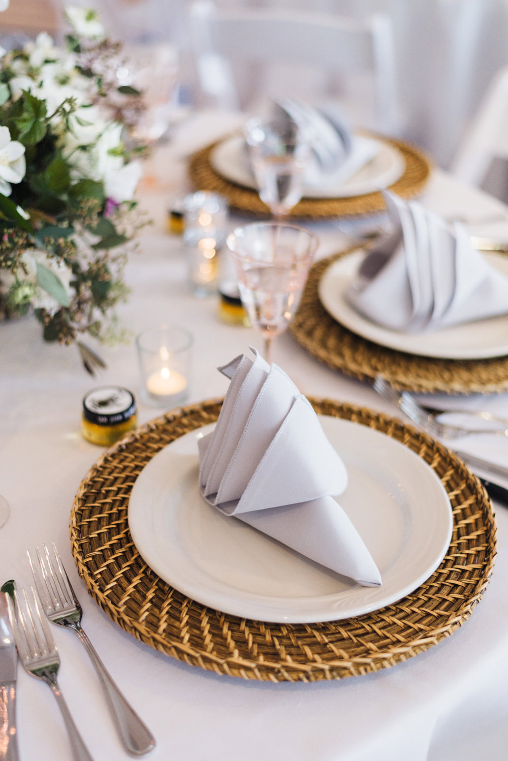 Unique napkin fold and rattan chargers set the tone for this romantic Roche Harbor wedding