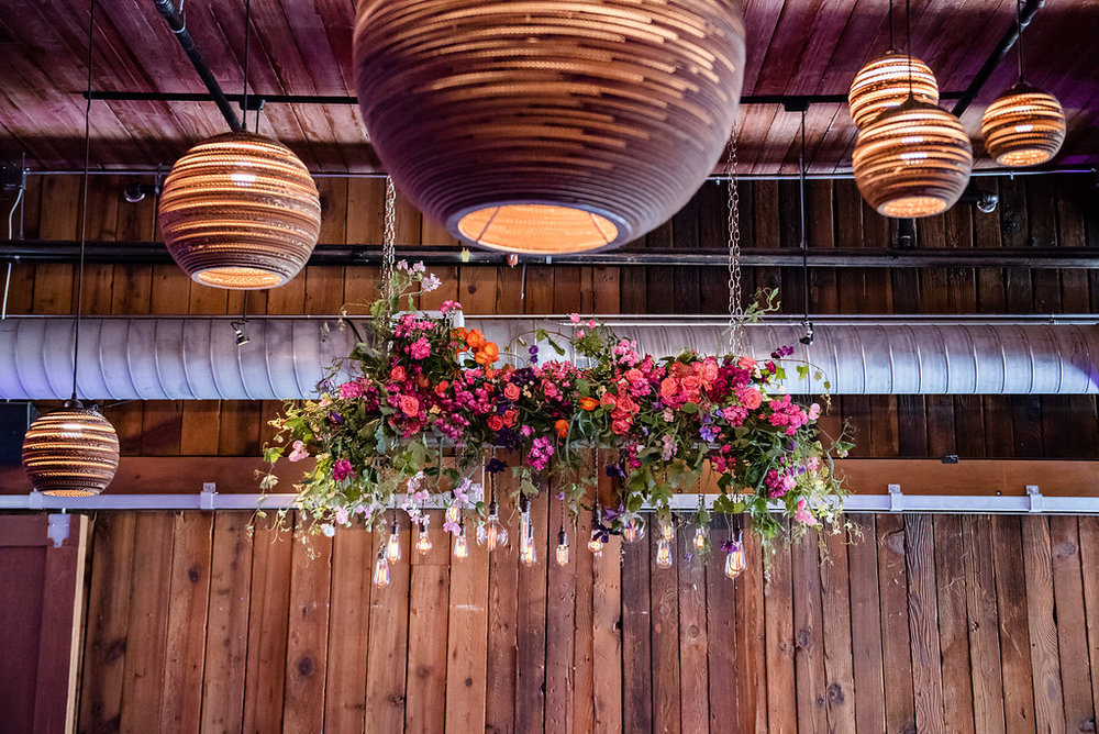 Unique Edison bulb and floral hanging wedding backdrop at this Within Sodo wedding