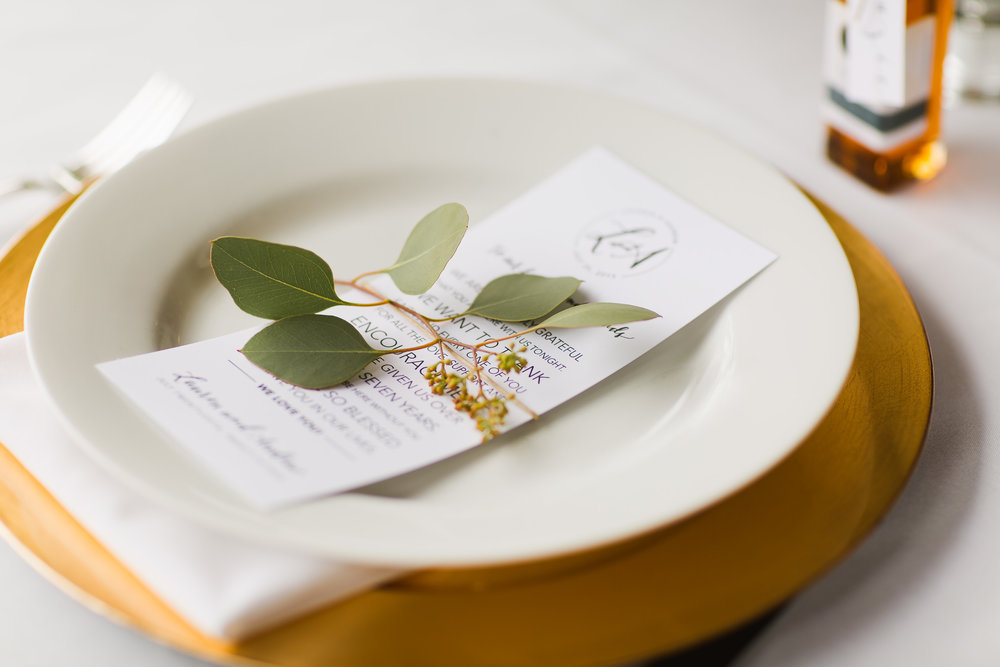 Gold charger place setting with eucalyptus sprig and menu