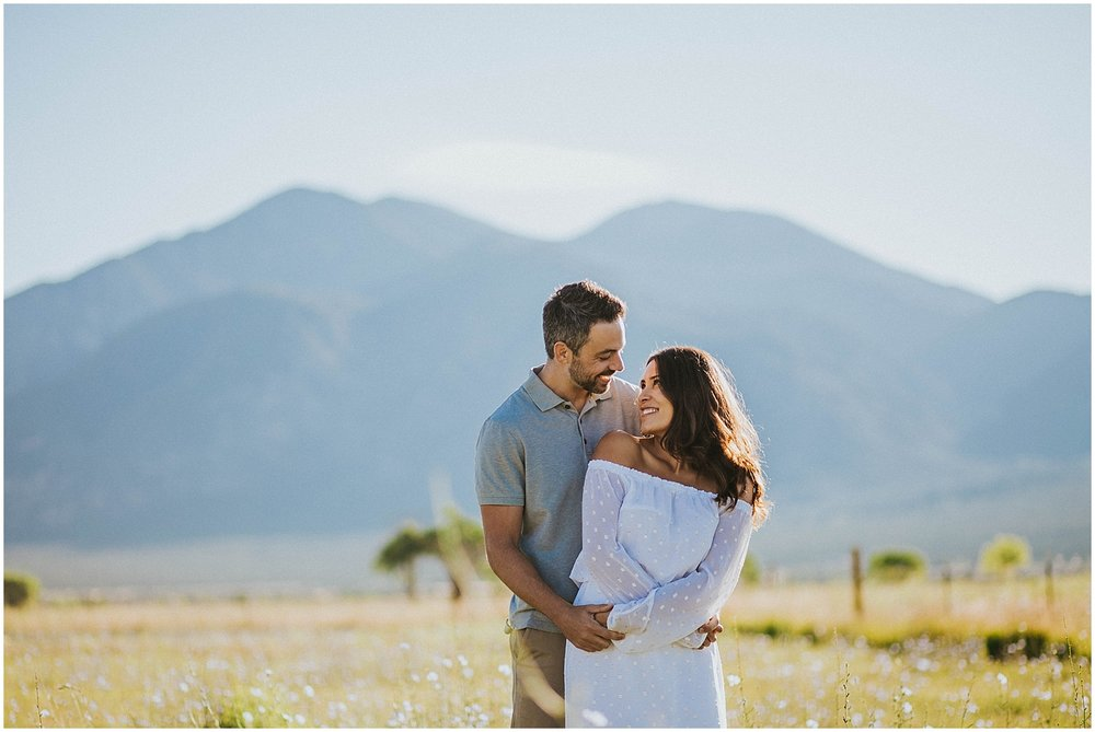 One of the best views of the Sangre de Cristo Mountains is at Overland Sheepskin Co. in Taos, New Mexico. The way the sun shines on the mountain in the early morning is true New Mexican magic at it's finest. Jade and Steve had an outfit change for this new location and again, it was PERFECT. Her short white dress complimented his engagement outfit fantastically. Talk about the ultimate engagement photo outfit inspiration. They are the definition of #relationshipgoals. | Jasper K Photography | New Mexico Engagement Photographer