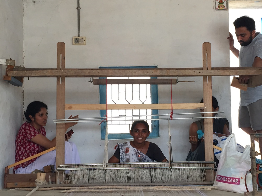 Arushi sits with Raji Ben and Shabri by the loom as Raji Ben creates a plastic weaving sample for The Initiative.