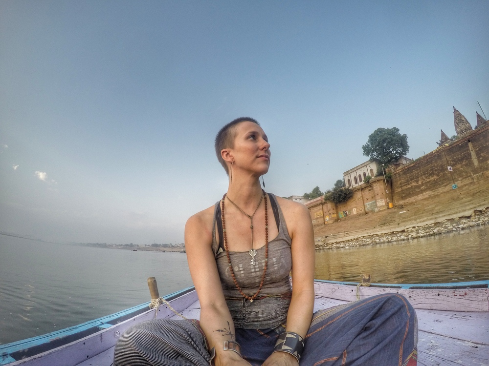 Megan floats on the Ganges in June, 2015, complete with a mala and building sense of awe.