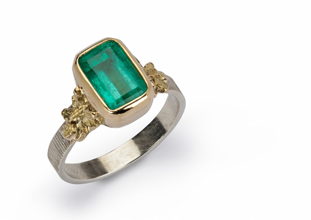 Emerald, oak leaf shoulders in 18ct. yellow gold on silver band