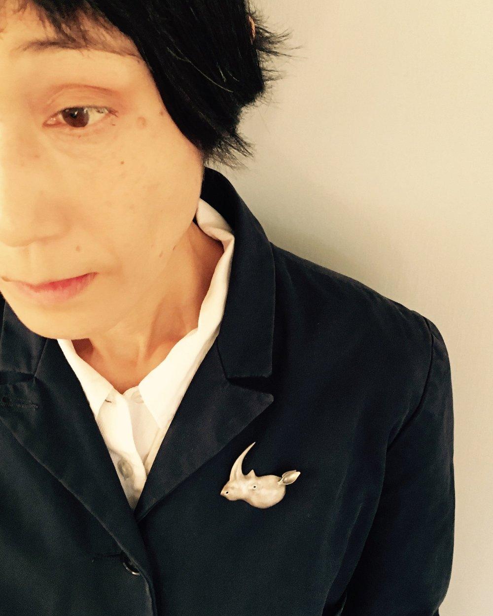 Rie wearing'My Horn is No Medicine: Rhino Head' brooch in silver, enamel paint, stainless steel pin size 44×39×10mmm