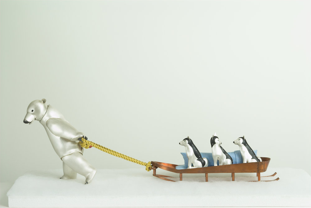 Composition ofPolar Bear Pulling Dog sledge (sculpture). Polar Bear - 150x110x100mm, silver, onyx, stainless steel spring. Husky (brooches x 3 ) in silver, onyx, acrylic, emerald, stainless steel pin. 60x40x10mm approx. Dog Sledge - 215x40x40mm, copper, fabric photo by Joël Degen