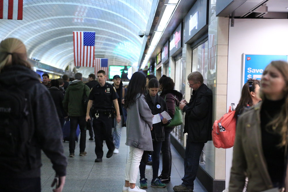Anna Chau and Eugenia Ramos invite participants to complete their belief ballots at New York Penn Station.JPG