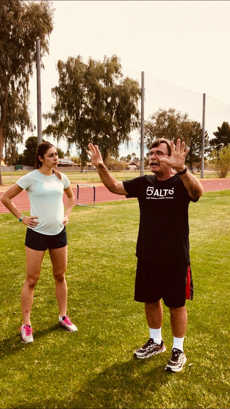 Coach  Dan Pfaff  pictured mid lesson teaching HPW Elite miler Rebecca Mehra.