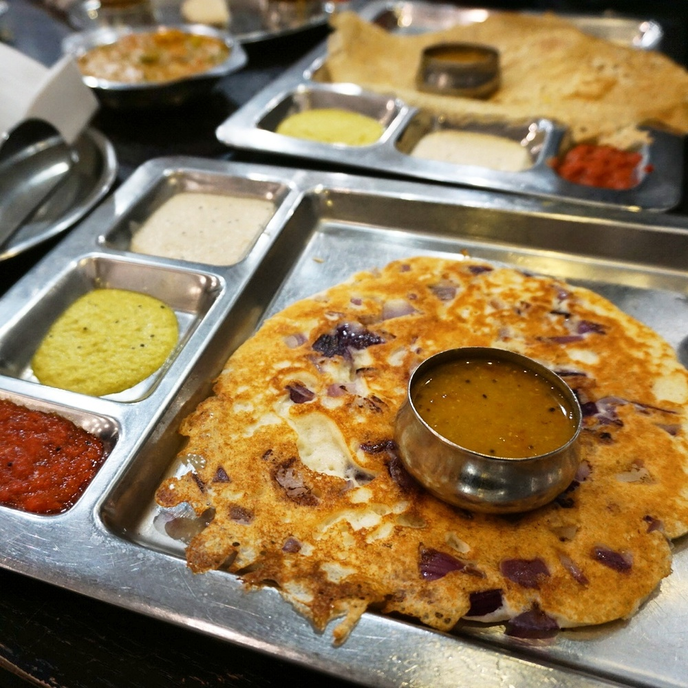 onion uthappam in the foreground, rava masala dosa in the background
