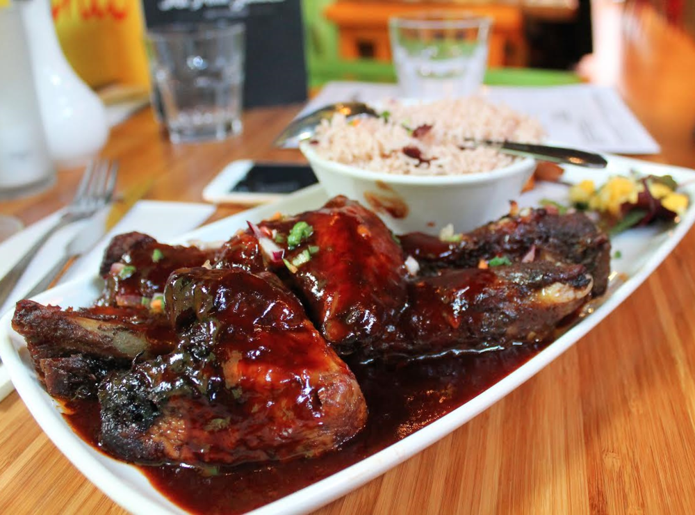 BBQ pork ribs, jerk chicken wings, and sides at Ma Petite Jamaica