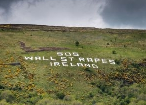 "Protesters write ""S.O.S. Wall Street rapes Ireland"" on a mountain outside Belfast."