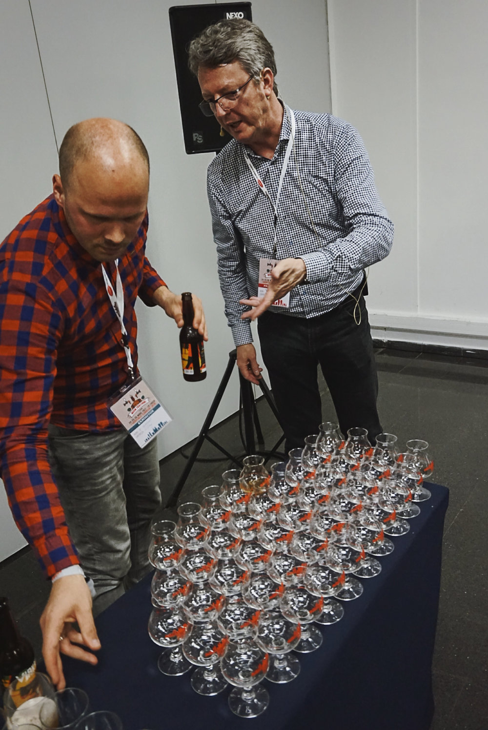 Kevin Vollebregt y Derek Walsh sirviendo ViaKrucis, una India Pale Ale de La Pirata, en las copas AnDer 1.0.