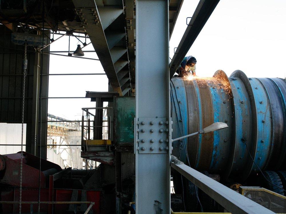 Usine de traitement du phosphate de Metlaoui. Région de Gafsa. 2012. Un ouvrier entretien l'équipement industriel qui permet de nettoyer le phosphate brute avec l'utilisation de milliers de litres d'eau par jour.