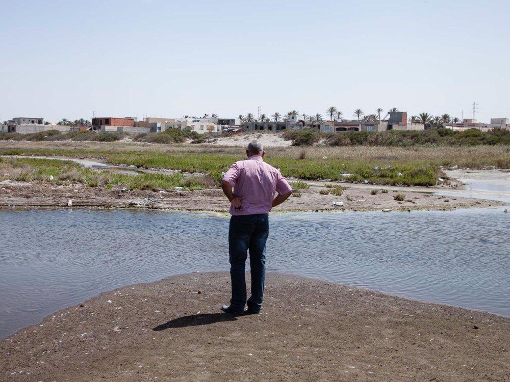 Plage de Chott Essalem. Gabès. 2016. Nazih Aoudi, armateur de Gabès et président de l'association de Chott Essalem pour le développement durable, observe une stagnation des eaux polluées sur la plage de Gabes. Régulièrement, il creuse des tranchées pour que l'eau s'écoule jusqu'à la mer a n d'éviter que moustiques et maladie ne se propagent.