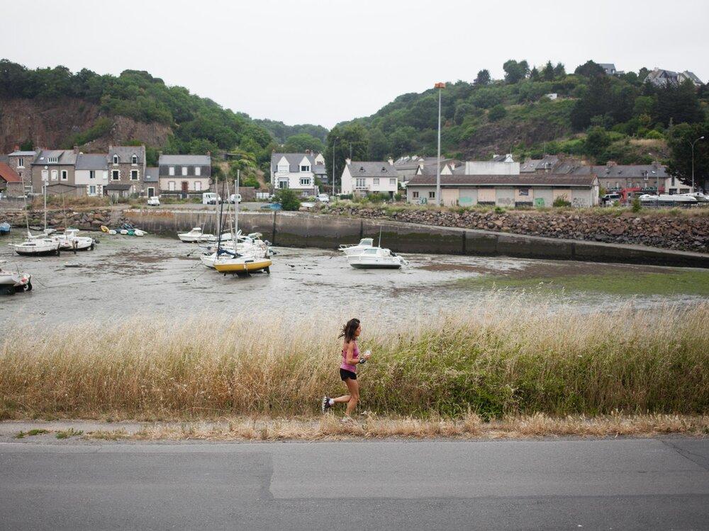 Saint-Brieuc. 22 juin 2017.  Une femme fait son jogging sur les bords du port Légué où de fortes odeurs nauséabondes se dégagent en raison de l'accumulation des algues vertes dans l'embouchure du port.