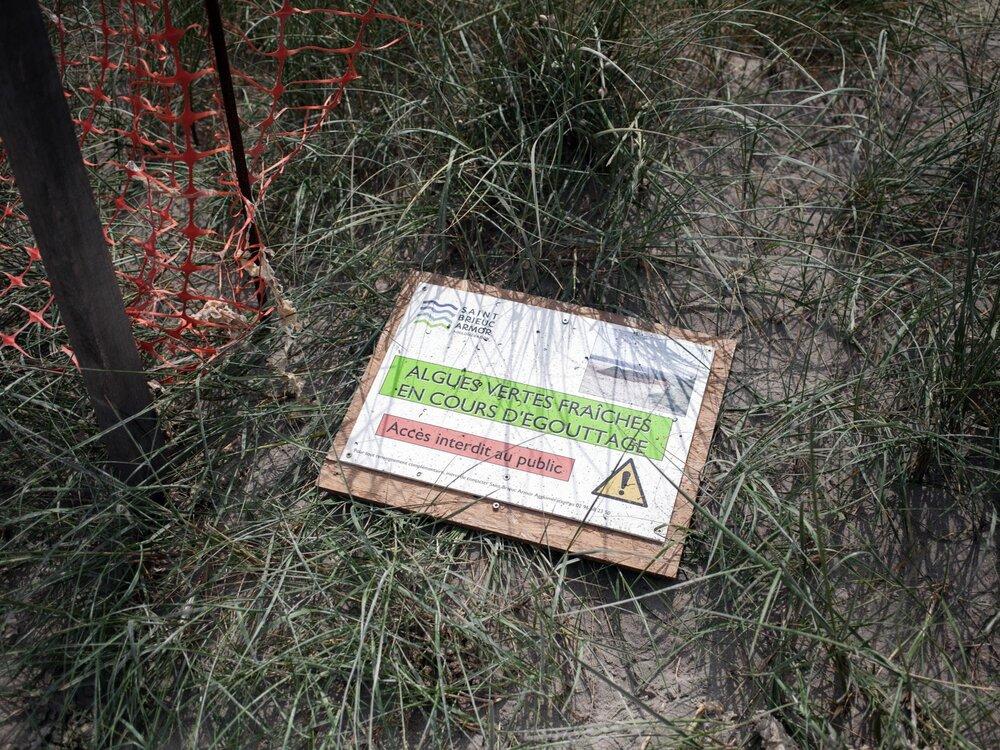 Hillion. Plage de Bon abris. 22 juin 2017.  Pancarte « Algues vertes fraiches en cours d'égouttage » sur la place de Bon Abris a Hillion.
