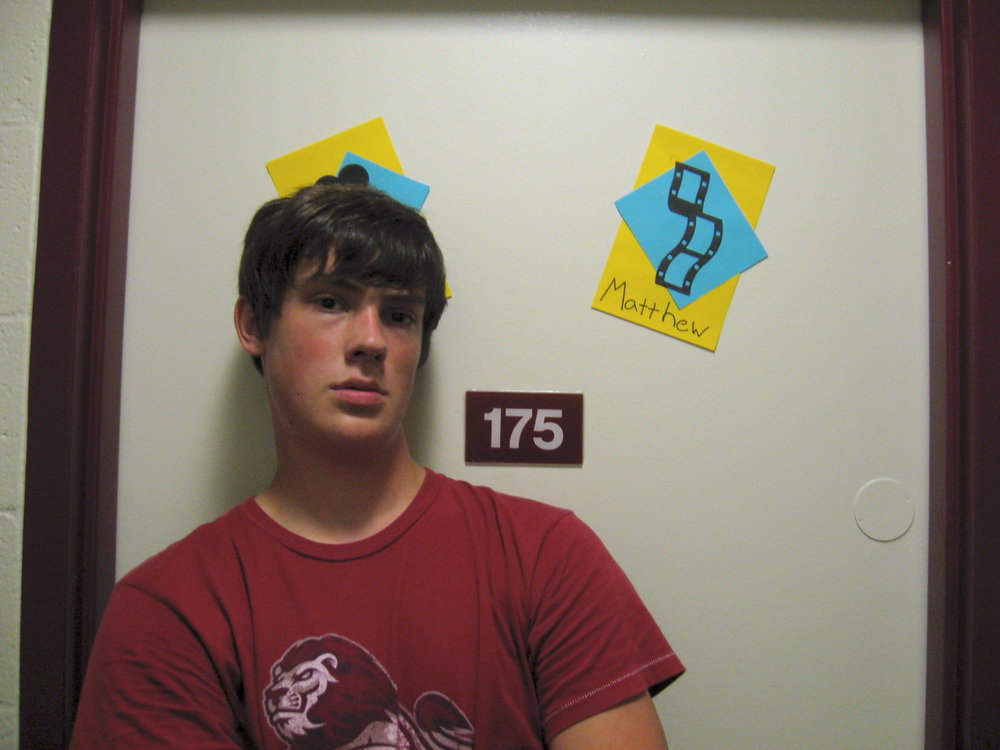 Matt standing in front of his dorm room, complete with filmstrip name tag.