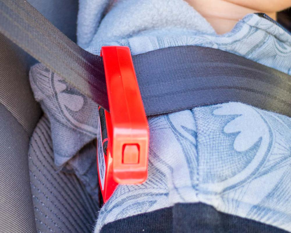 At the back of the foldable booster seat for travel is a long strap that can be hooked onto the shoulder belt of the seat belt. There is a small latch on the shoulder hook that allows the strap length to be adjusted so that the shoulder belt can be pulled down to the proper height for the child.