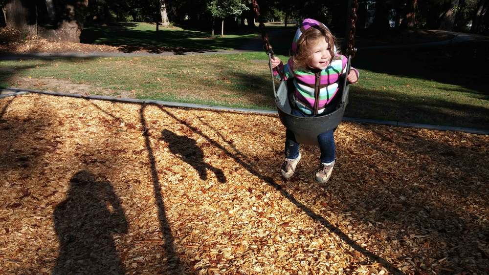 Happy girl swinging between sessions of planting bulbs.