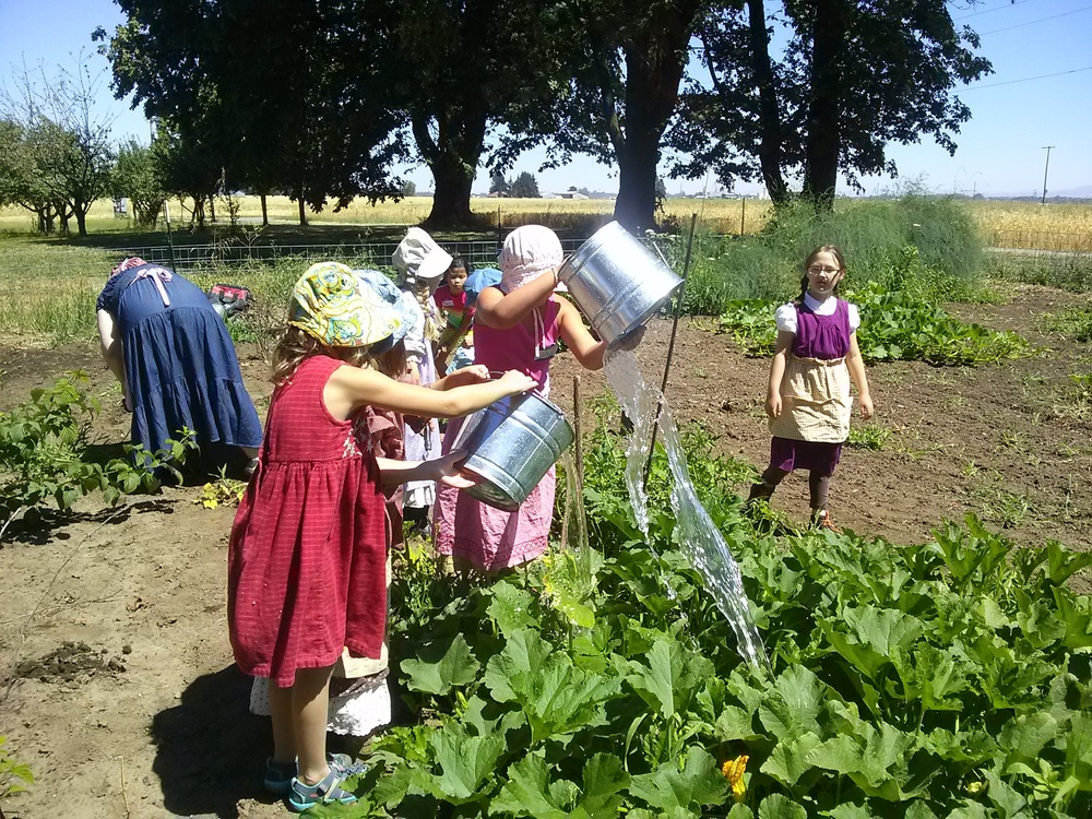 Children water plants in the garden the old fashioned way during summer camps.