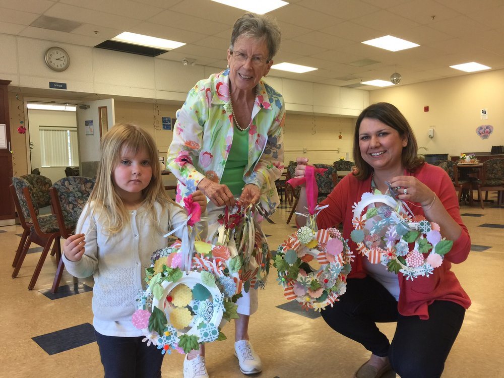 Addie delivering 60 paper flower wreaths to the Gilmore Senior Center. Yvonne Griffin (left) and Rebecca Todd (right).