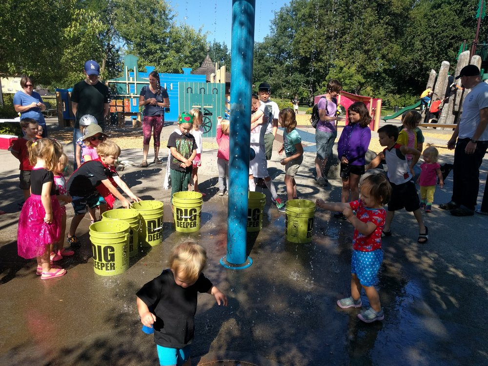 Filling up buckets at the splash pad part of the playground.