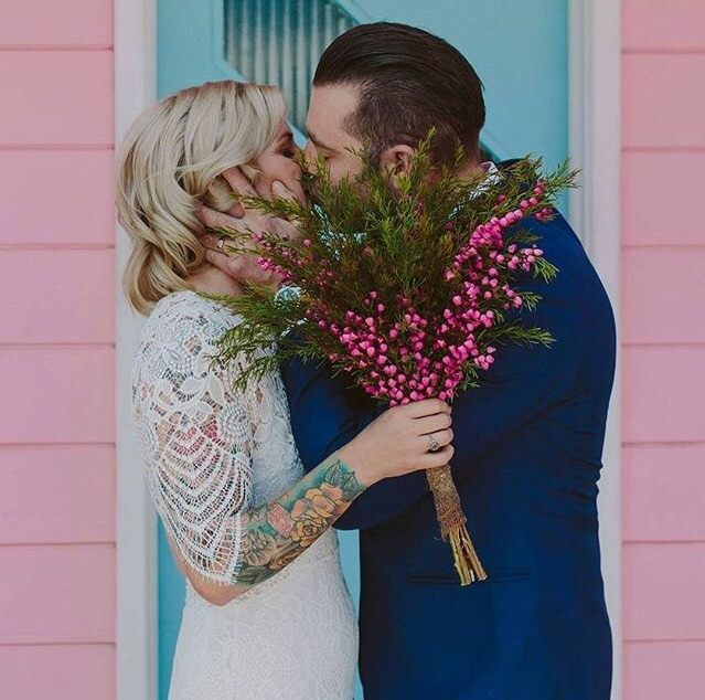 Instead of hiding the tattoos, the white colour of the dress and the see-through laces are highlighting the coloured details of this brides beautiful tattoos.