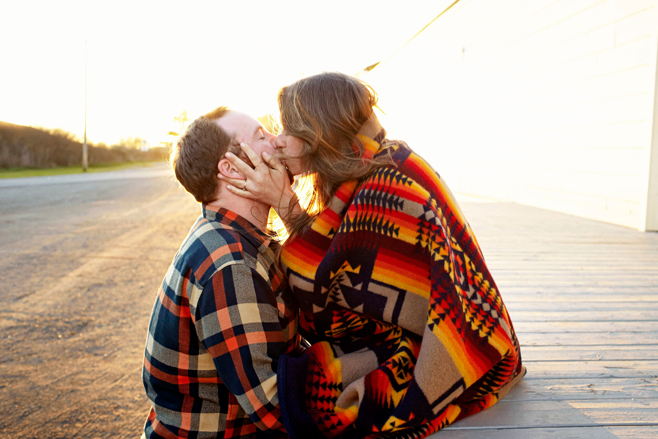 Road trip engagement kissing in Pendleton blanket