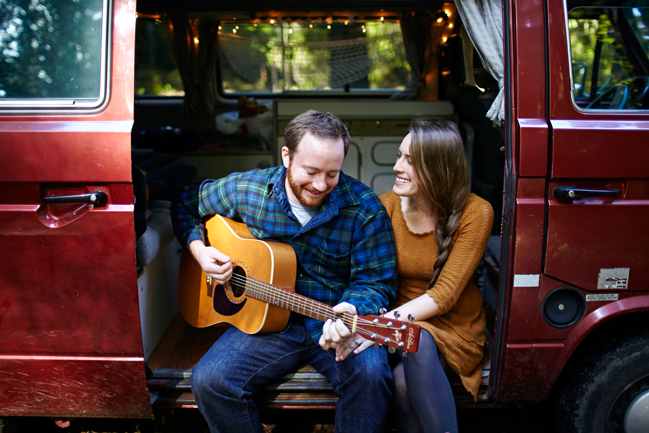 Road trip engagement playing guitar in VW