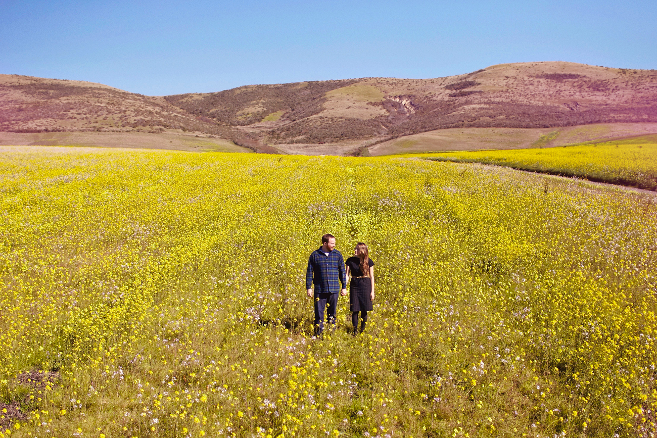 Road trip engagement standing in field of flowers