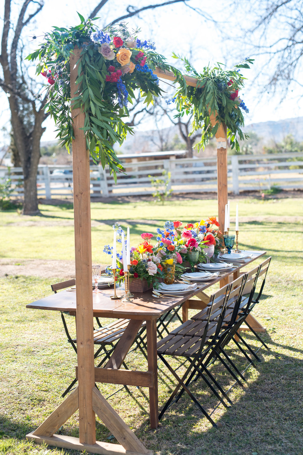Farm Table with Floral Overhead and Colorful Centerpieces
