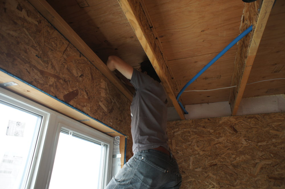 Eric air sealing the rim joist area with foam and caulk.