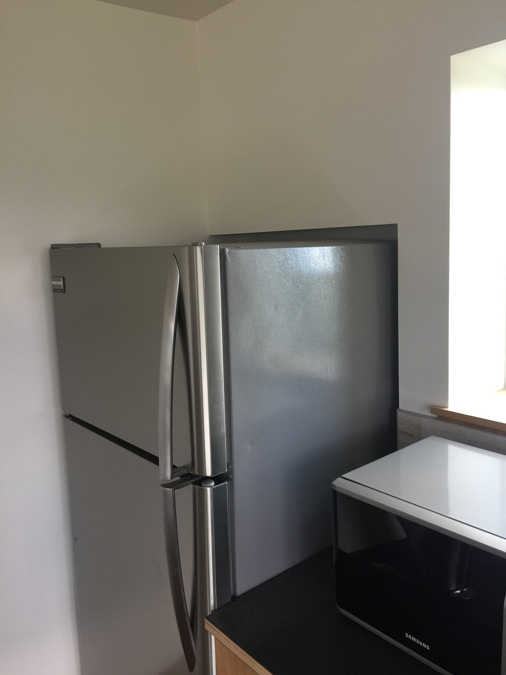 Firring out the kitchen wall for the makeup air vent also allowed us to inset the refrigerator so the door is in line with the edge of the counter, almost like a countertop-depth appliance.