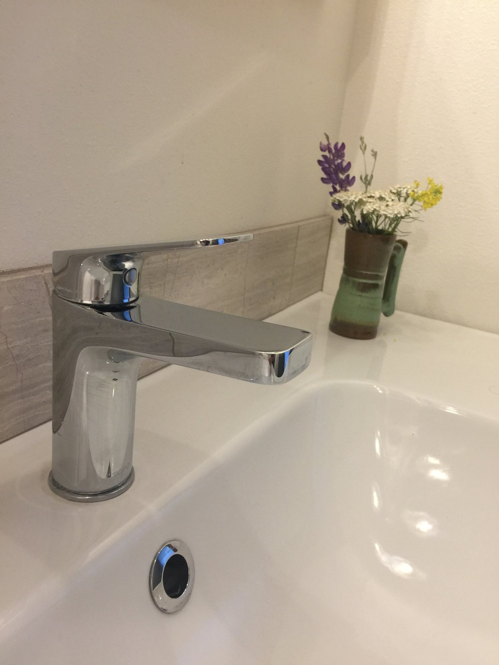 We chose the new Toto Oberon faucet, which is WaterSense Certified and has a maximum flow rate of 1.5 gpm. We paired this high-quality faucet with a low-cost Ikea sink. If you're designing a bathroom on a budget, it's wise to invest in quality faucets and fixtures and save money on the sink.