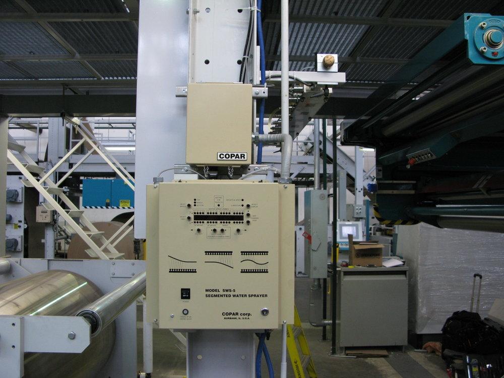 El panel del control y la barra rociadora instalados en una corrugadora