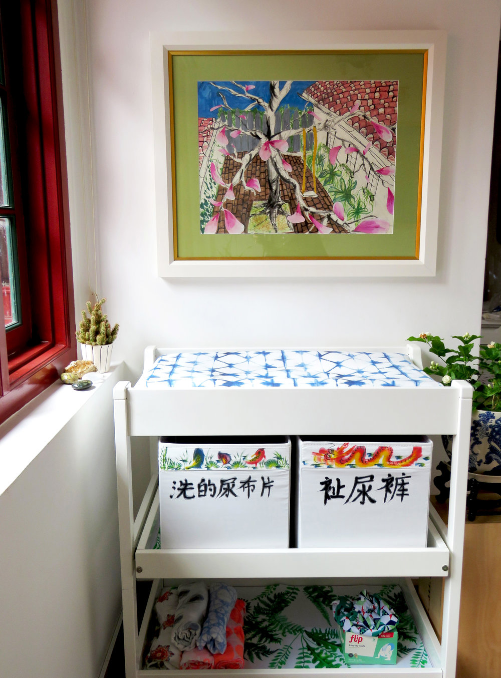 up-cycled changing table, Mandarin calligraphy-labeled boxes for cloth diapers and jasmine plant.