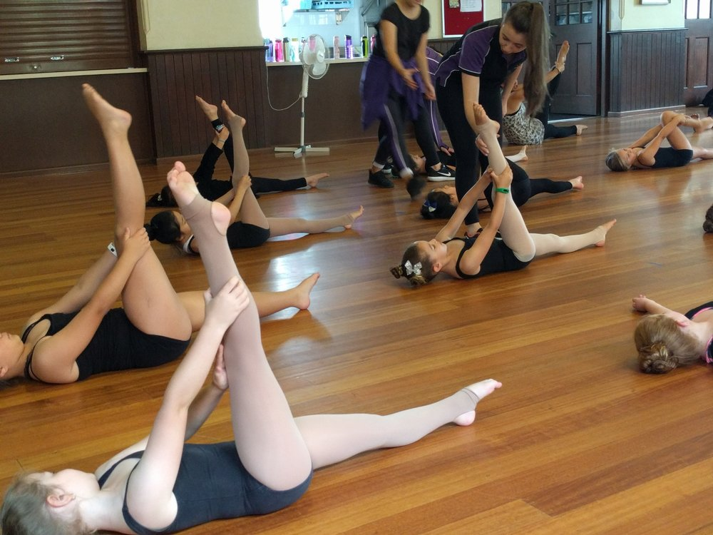 Junior's team preparing their splits while corrections hips posture