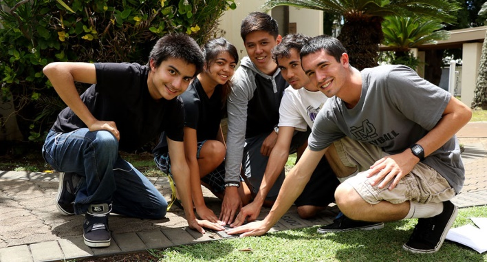 """Seniors and friends, (l-r) David Ybarra, Lin Shibata, Logan Santiago, Ethan Kaimalu Diaz, and Jared Miller place hands on the """"2016"""" paver just laid in the Viriliter Age Pathway on the Damien Memorial School campus."""