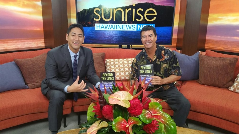 "Damien Alum Rusty Komori '87 with Sunrise host Steve Uyehara '94. Rusty appeared on Sunrise this morning with Steve to promote his first published book, ""Beyond the Lines"". He had successful book signing at the Ala Moana Barnes & Nobles tomorrow Feb. 10th from 1-2pm during the book fair. He sold over 100 copies of his book and generated over $10,000 in funds for one of Damien's scholarship programs."