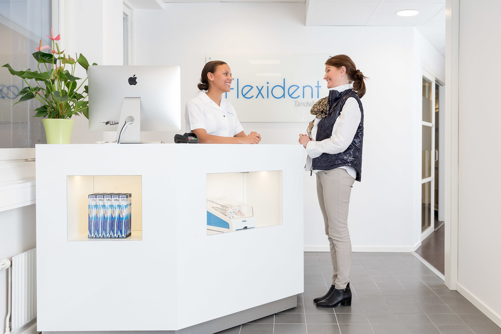En receptionist som tar emot en patient på vår tandklinik i Bromma.