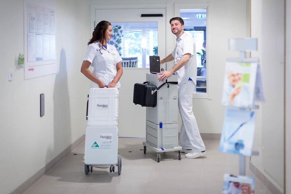 Två tandläkare som är på väg med utrustning för att utföra mobil tandvård hemma hos en patient.