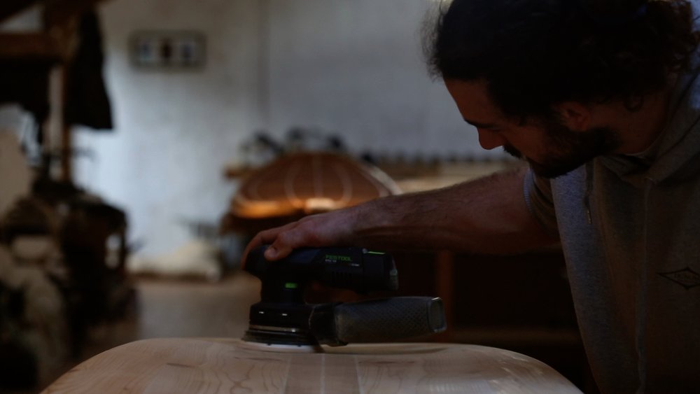 Alen shaping the wooden surfboard using a range of different Festool sanders